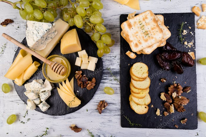 Cheese plate. Assortment of cheese with walnuts, bread an honey on stone slate plate.