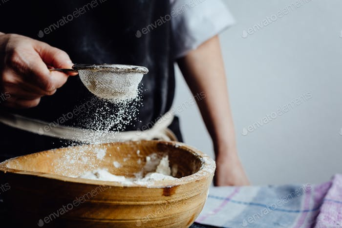 Person covering pastry with flour