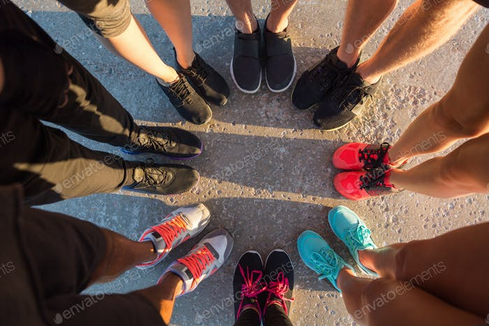 Runners standing in a huddle with their feet together