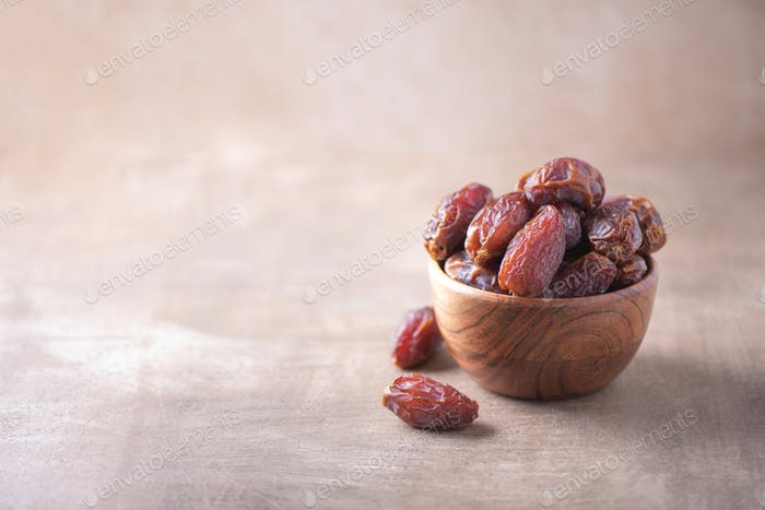 Dried date fruit in wooden bowl on wood textured background. Copy space. Superfood, vegan