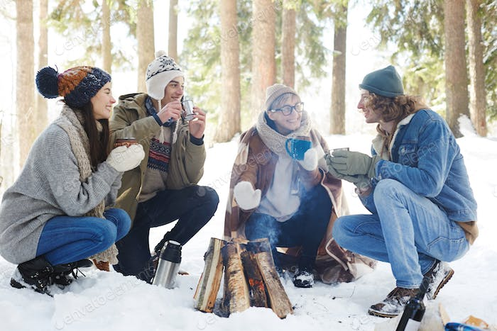 Young People Enjoying Drinks in Winter Forest