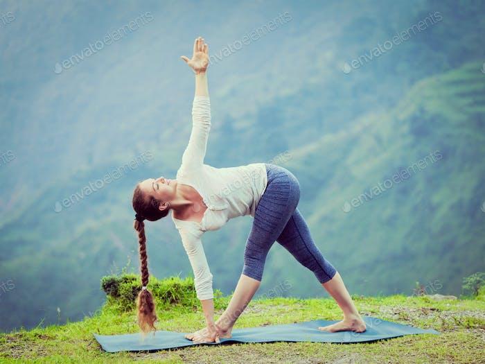 Frau tut Ashtanga Vinyasa Yoga Asana Parivrtta trikonasana