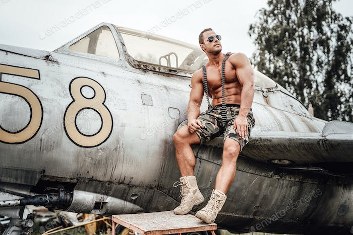 Bodybuilder from USA looking away with old airplane behind
