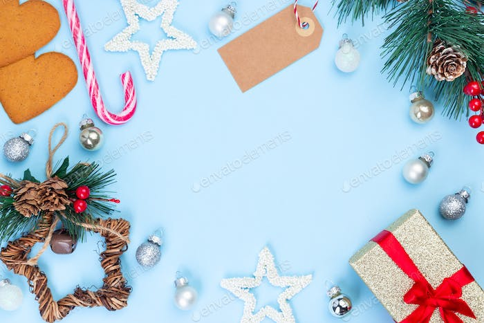 Festive frame with gift box, pine branch, empty shopping tag, stars, candy cane