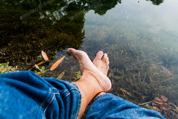 Legs and feet relaxing in front of serene fresh water pond