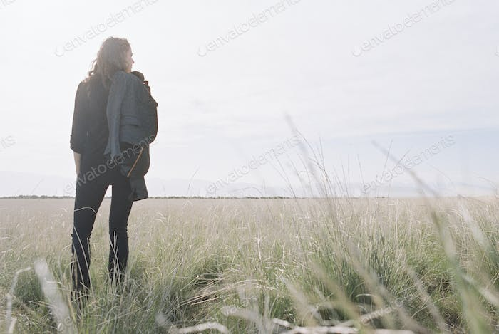Woman standing looking to the horizon, carrying a jacket and backpack.