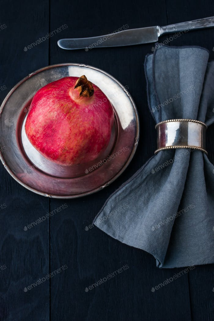 Pomegranate with old vintage dinnerware