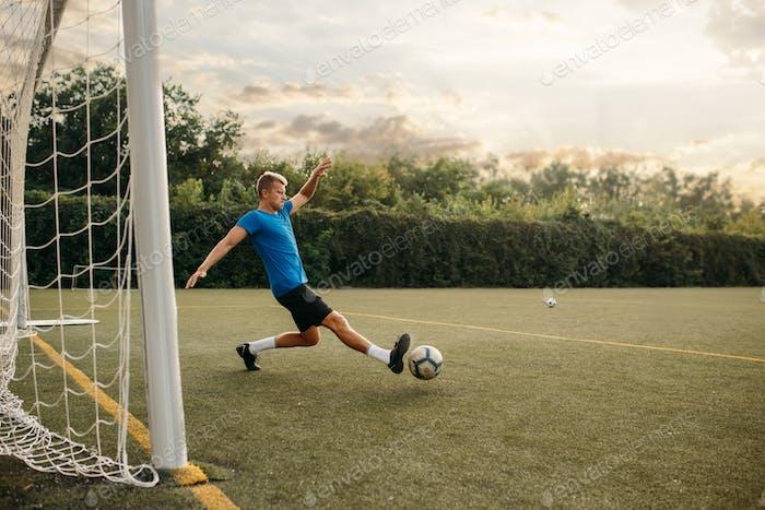 Male soccer goalkeeper hits the ball