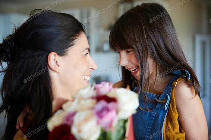 Young white girl giving her mother flowers as a gift on her birthday, close up, selective focus