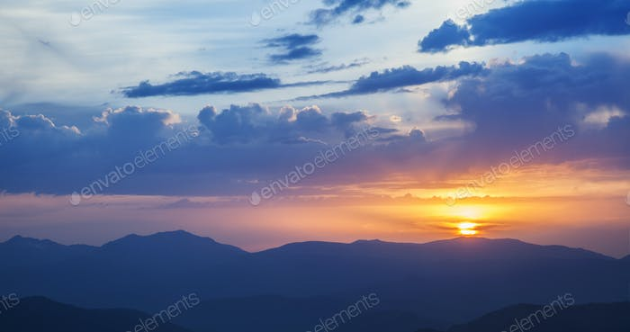 Mountain ridges at sunset against the sky with clouds