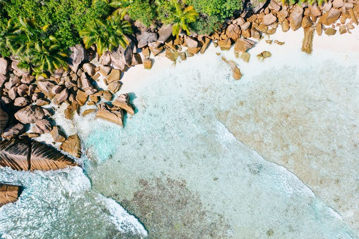 Aerial drone bird eye shot of beautiful paradise tropical Anse Cocos beach at La Digue, Seychelles