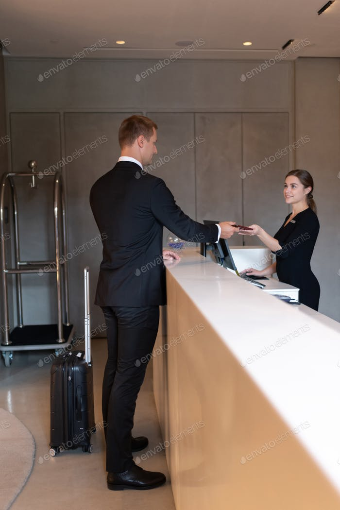 Businessman passing key to receptionist for checkout in hotel