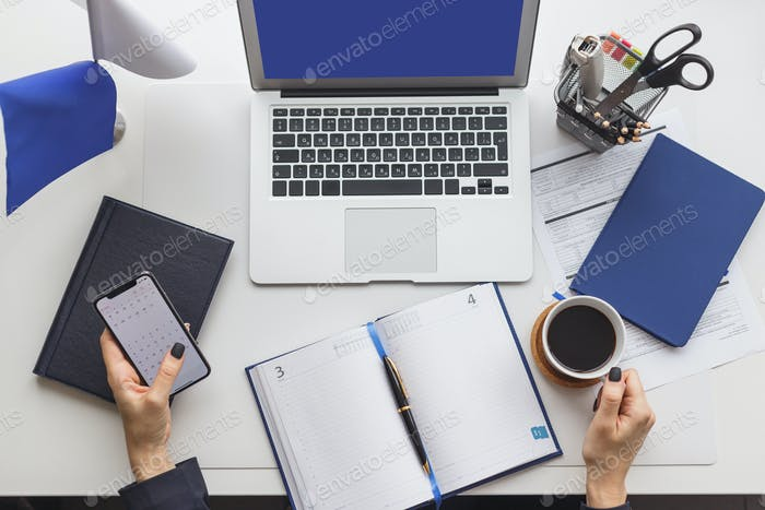Nonstop working office woman with cup of coffee at her workplace. Deadline concept, top view