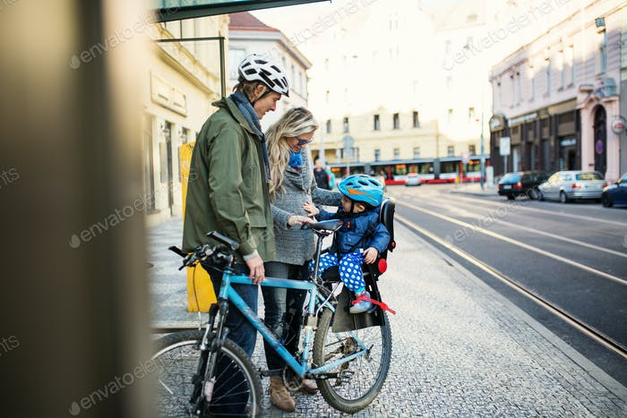 A small toddler boy sitting in bicycle seat with young parents outdoors in city.