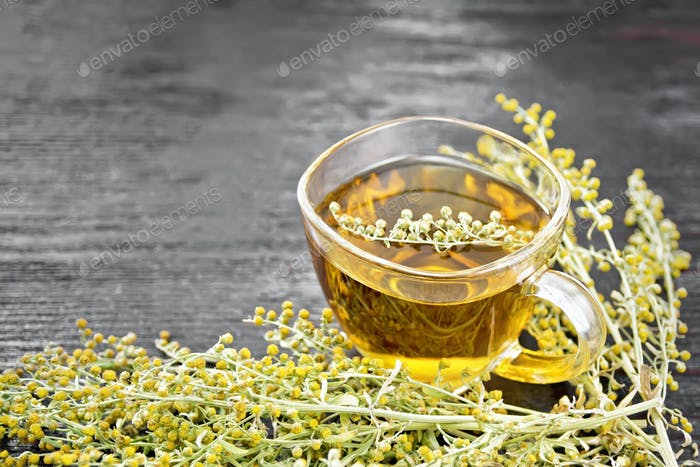 Tea of gray wormwood in glass cup on board