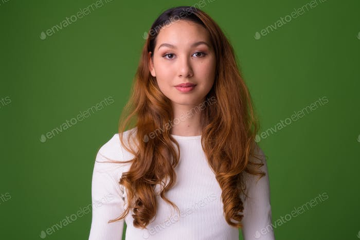 Young beautiful Asian woman against green background