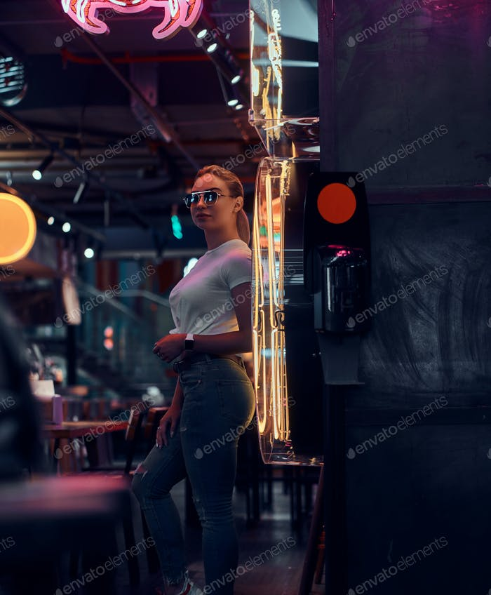 Attractive woman in sunglasses at neon bar is posing for photographer.