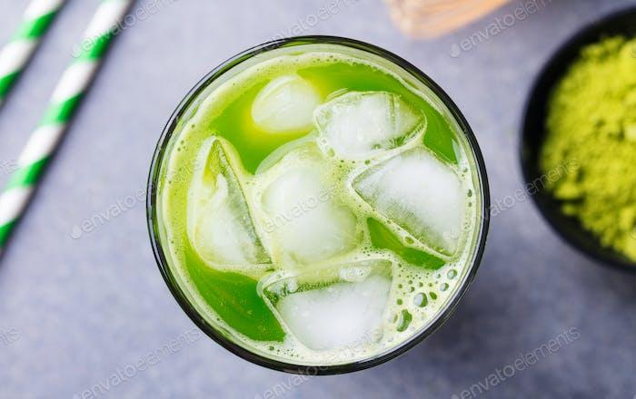 Matcha, grüner Eistee im hohen Glas. Grauer Hintergrund. Nahaufnahme.