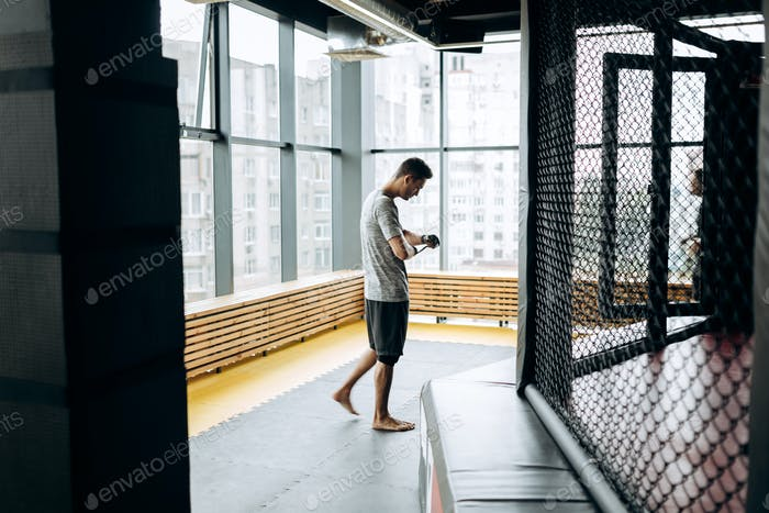 Guy dressed in the grey t-shirt wraps a hand bandage on his hand in the boxing gym against the
