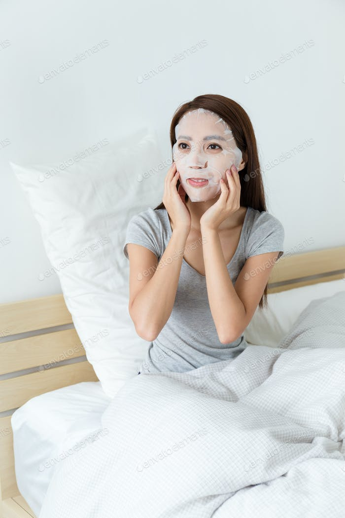Young lady do masking on bed
