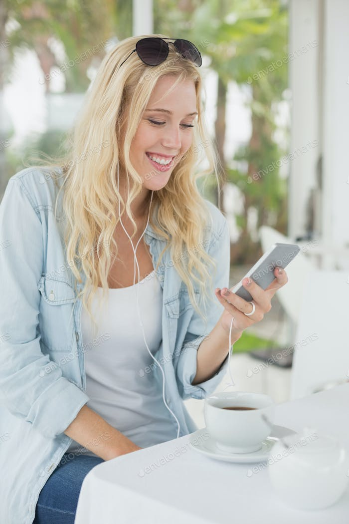 Pretty blonde sitting at table having coffee sending text on the cafe terrace on sunny day
