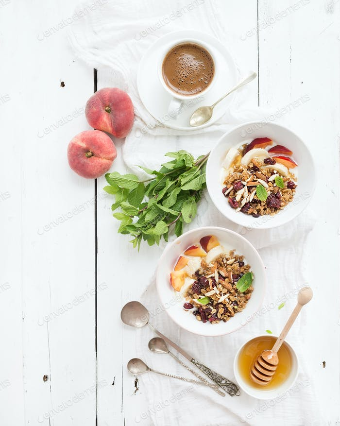 Healthy breakfast. Bowl of oat granola with yogurt, fresh fruit, mint and honey