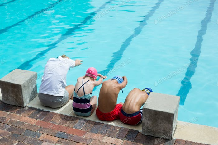 Swimming instructor teaching students at pool side