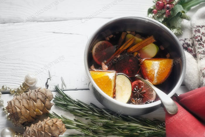 Mulled wine with different spices  and fruits in the pot horizontal