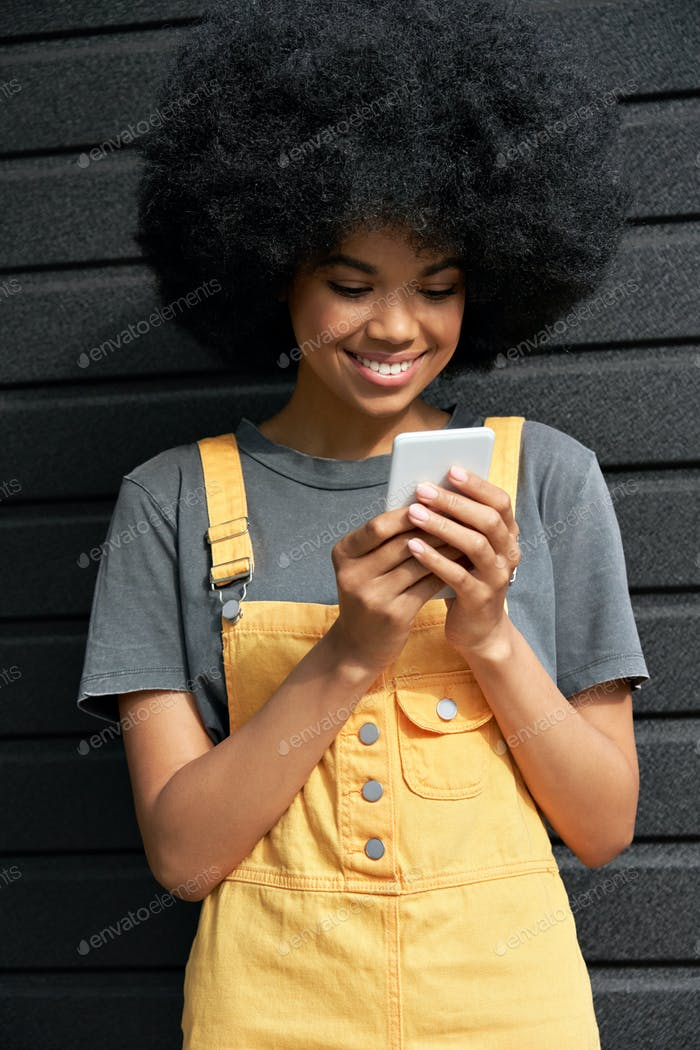 Smiling African young hipster  lady with Afro hair using smartphone.
