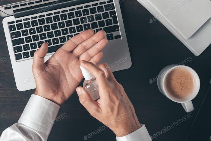 Geschäftsmann mit Desinfektionsspray, um Hände zu desinfizieren, während der Arbeit Büro Schreibtisch