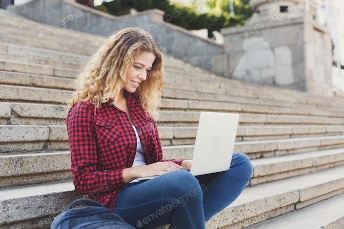 Sonriente estudiante chica sentado en las escaleras Uso Ordenador portátil al aire libre