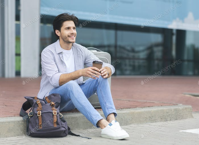 Young male traveller sitting near airport terminal with coffee