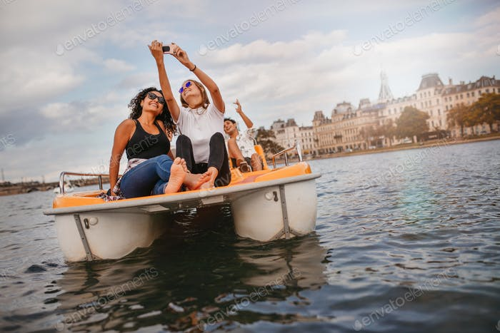 Young friends taking selfie on pedal boat