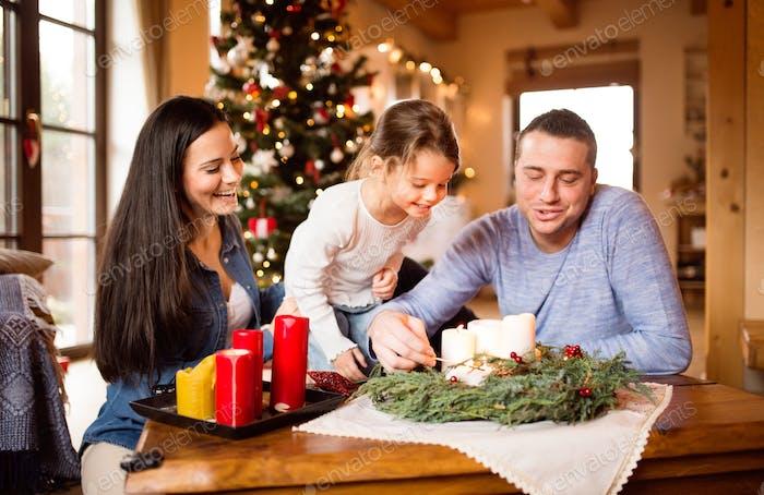 Junge Familie zündet Kerzen auf Adventskranz. Weihnachtsbaum