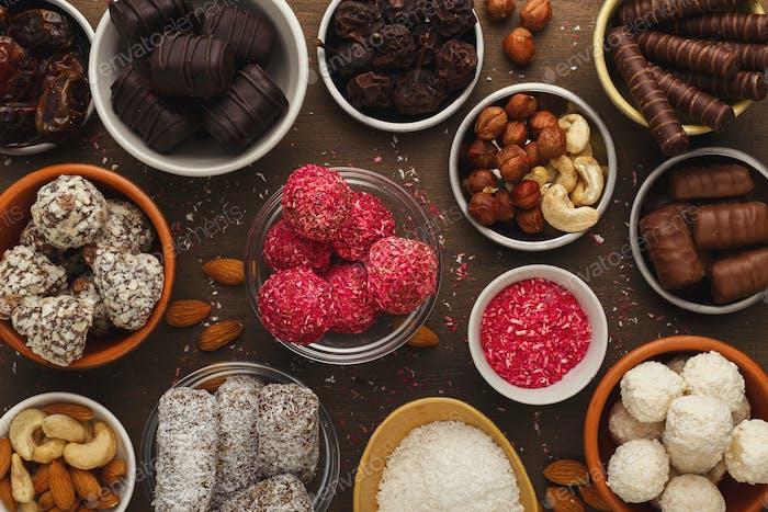 Holztischplatte mit einer Auswahl an gesunden Süßigkeiten und Nüssen