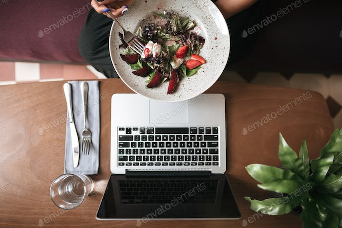 Salad and laptop on table at cafe