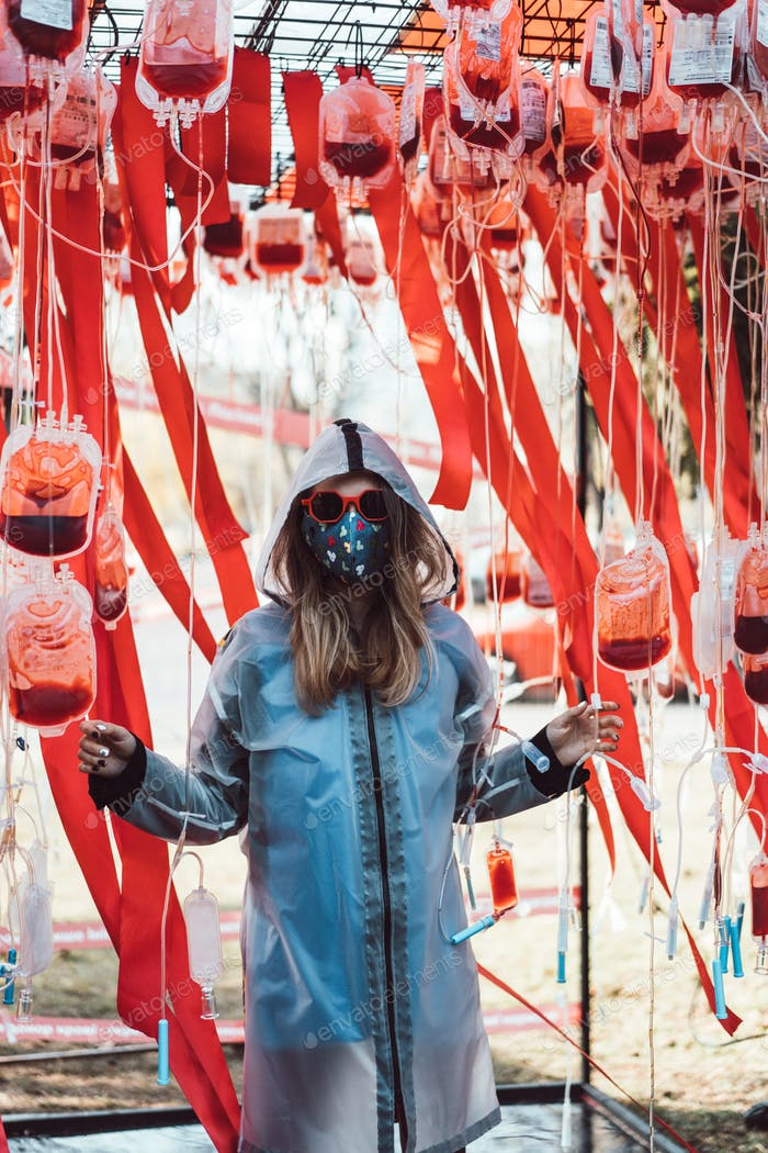 Girl in sunglasses, mask posing among empty bags with blood