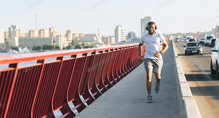 Joyful black runner jogging down the highway bridge
