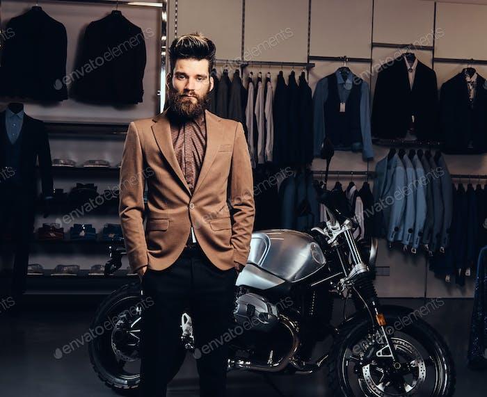Модный человек позирует рядом с ретро спортивный мотоцикл в магазине мужской одежды.