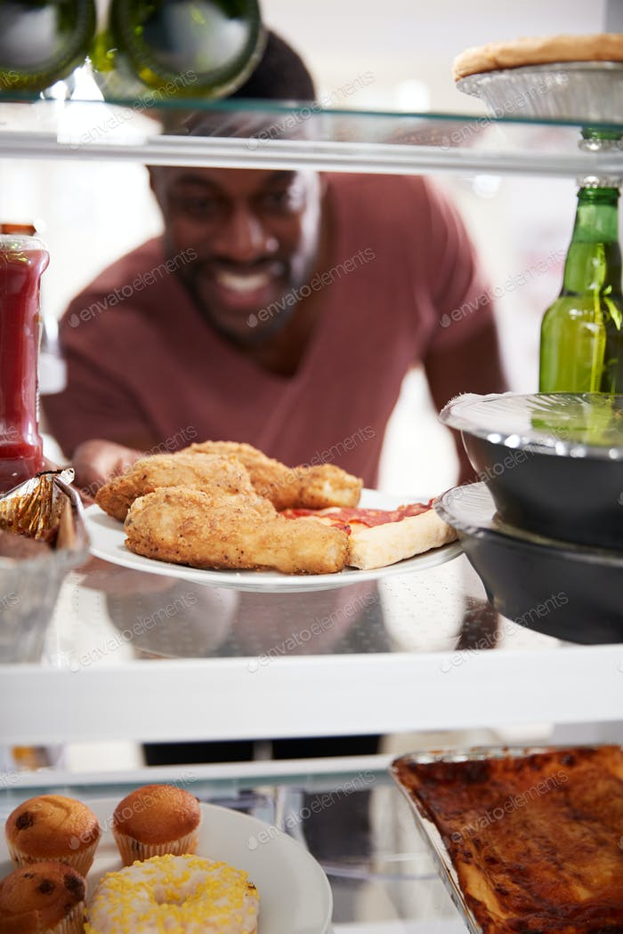 View Looking Out From Inside Of Refrigerator Filled With Takeaway Food As Man Opens Door
