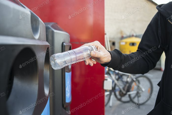 Man hand throwing plastic bottle into recycling bin
