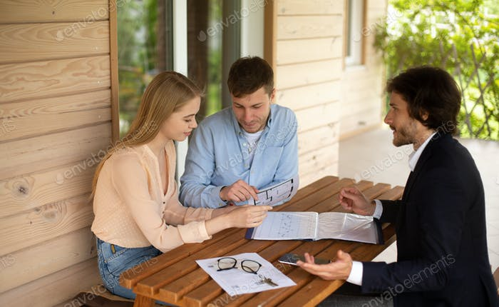 Real estate broker showing house project to young family on porch