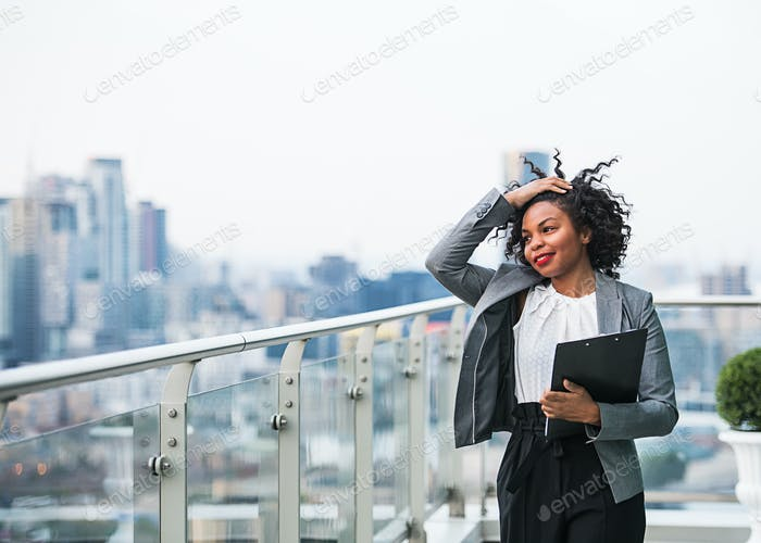 A portrait of a businesswoman with clipboard standing on a terrace.