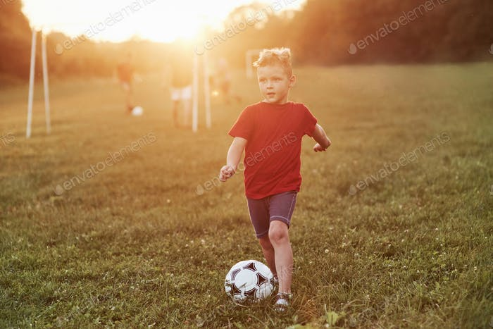 Where the rest of my team is go. Boy plays football at sunny warm day and going to score a goal