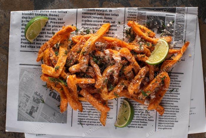Draufsicht auf Salzige Pommes Frites und Limettenscheiben auf Zeitung mit Text