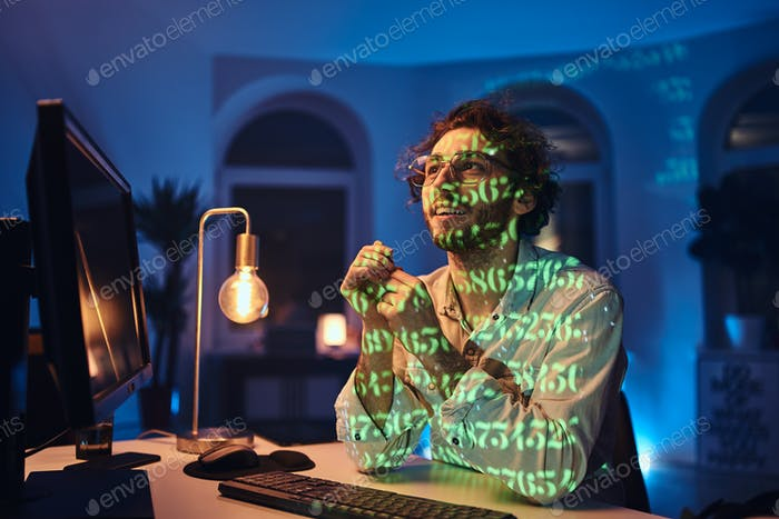 Кавказский фрилансер в очках и компьютере работает в темном офисе