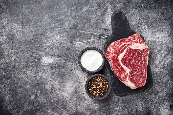 Raw marbled ribeye steak and spices
