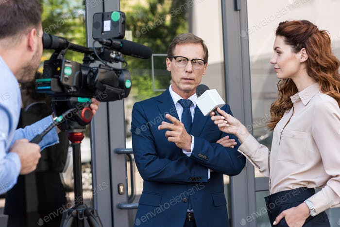 professional cameraman and news reporter talking with serious businessman