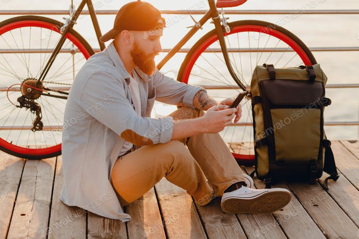 handsome bearded man traveling with bicycle in morning sunrise using phone