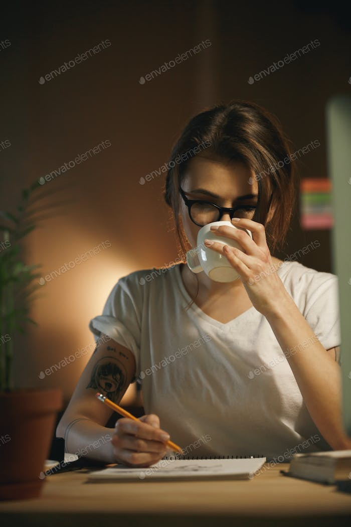 Serious young woman designer writing notes and drinking coffee